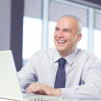Geschäftsmann sitzt am Laptop und lacht seinem Kollegen zu.
