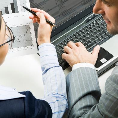 Ein Mann und eine Frau arbeiten zusammen an einem Laptop und diskutieren Statistiken.