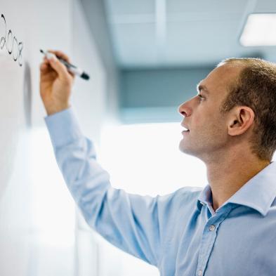 Ein Mann im hellblauen Hemd schreibt etwas an ein Whiteboard.